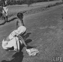 A womans collects fallen grains of food from the road. (Picture by life.com; courtesy - oldindianphotos.blogspot.com.). Click for larger image