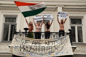 "Four young Ukrainian women went topless on the balcony of the Indian envoy's residence in Kiev with placards pronouncing ""Ukraine is not a bordello"" and ""We are not prostitutes"".  The Femen quartet are 'famous' for topless protests against topics ranging from sex tourism to Silvio Berlusconi's peccadilloes. This time they were protesting the alleged tightening of visa rules by the Indian mission in Kiev for Ukrainian women in the 15-40 age group.  
