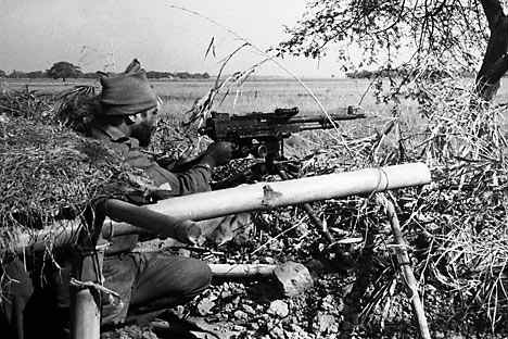 An Indian Army machine gunner fires at Pakistani positions in a village across an open field, 1,500 yards inside the East Pakistan border at Dongarpara on Dec. 7, 1971. Both sides have taken trenchlines position, in an attempt to prevent each other's moves. This picture was taken about 200-miles North East of Calcutta. |  Source: AP; Courtesy - RIR