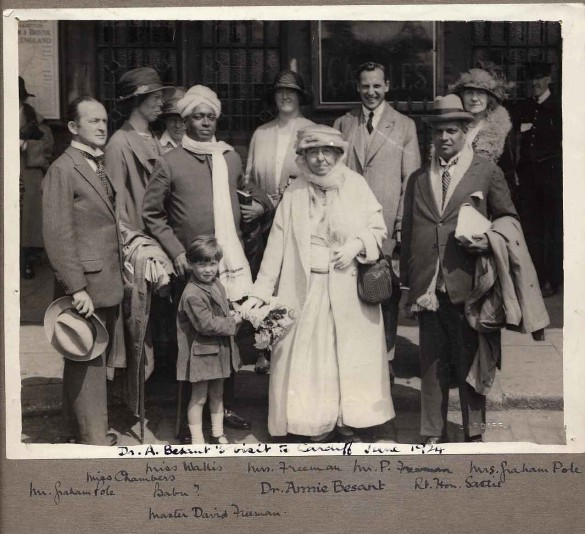 Annie Besant in Cardiff (1924) with two Theosophical Society officials from India greeted by Cardiff Theosophists at Cardiff Central Station. Back Row: (Left to Right) Miss Chambers (looking to right) Miss Wallis (almost hidden), Mrs Freeman, Mr Peter Freeman (General Secretary, Wales), Mrs Graham Pole. Front Row: (Left to Right) Mr Graham Pole, Babu, Dr Annie Besant, The Right Honourable Sastie. Lad presenting flowers is David Freeman, son of Peter Freeman.